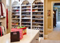 Luxury master closet with shoe shelves, a center dresser and dressing room