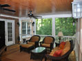 Inside a custom screened porch created by Hughes-Edwards Builders
